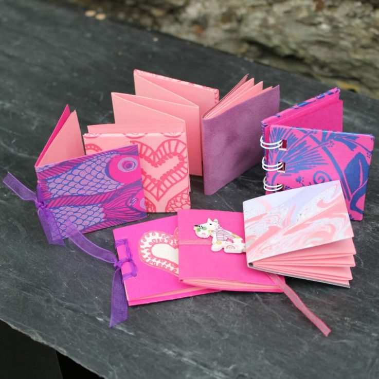 7 pink handmade tiny books with assorted bindings and designs. Handbound books in a shiny silver box